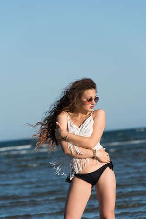 wet t shirt: Woman with long curly hair wear bottom bikini, sunglasses and white shirt, standing in sea water. Sea and sky as background