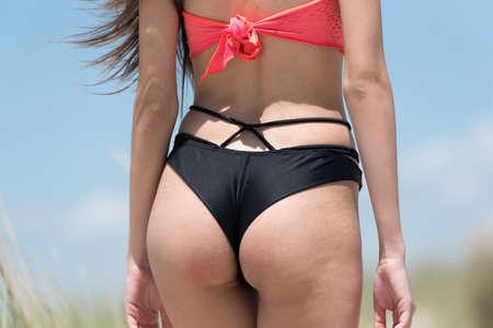 abdomen plano: Mujer con bikini de desgaste plana del estómago, cerca foto en las caderas, de pie entre las plantas Ammophila