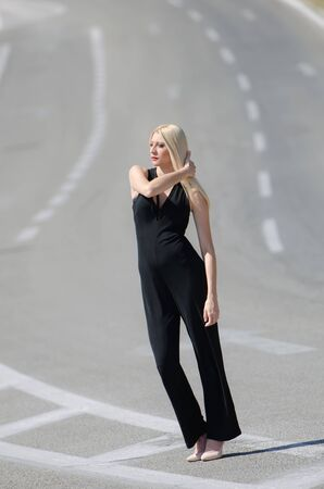 outside shooting: Outstanding model with a slim body do a fashion shooting on the high speed road wearing a black neck jumpsuit