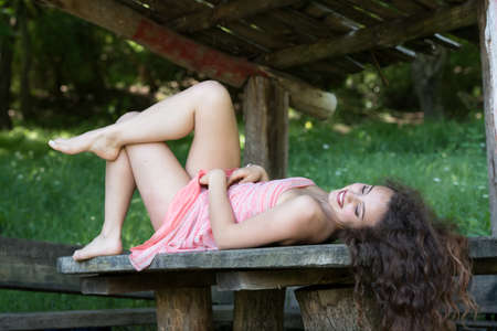 Cute lady wear a pretty summer dress, lying on a wooden kiosk table deep in the forest