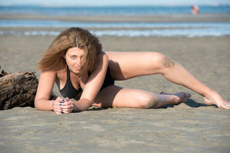 Blond woman wear black bikini lean on a tree trunks that washed up by the sea