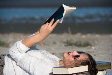 bookish: Woman with long curly hair reading a book at the beach