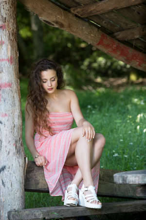 Cute lady wear a pretty summer dress, sitting on a wooden kiosk in the mountain Stock Photo