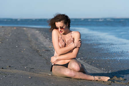 wet t shirt: Woman with long curly hair wear bottom bikini, sunglasses and wear spaghetti strap, sitting on the beach. Sea as background
