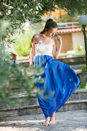 Barefoot girl wear blue and white dress and play with it, olive tree in forground