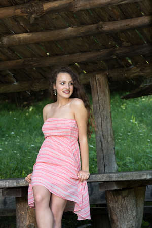 Cute lady wear a pretty summer dress, leaning against a wooden kiosk table deep in the forest
