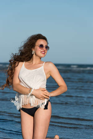 Woman with long curly hair wear bottom bikini, sunglasses and white shirt, kneeling in sea water. Sea and sky as background