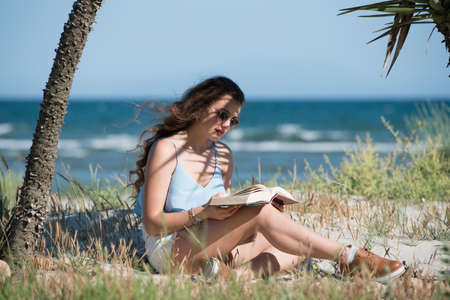 bookish: Woman with long curly hair wear spaghetti strap and shorts. Read a book as she sitting on the beach between of palm trees. Sea, sky and greens as background Stock Photo