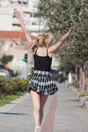 Blond woman with little pigtails and long slim legs wearing check mini skirt run at sidewalk cityscape at the background