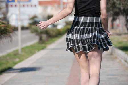 Woman run away at sidewalk with her mini skirt jump up and down Banco de Imagens