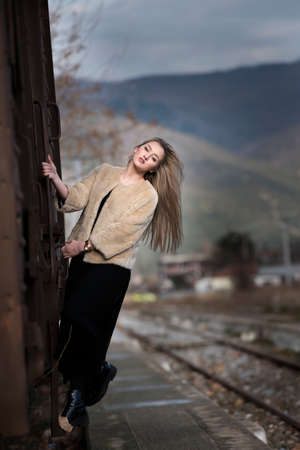 climbed: Blond young woman wear sheep jacket and black long skirt climbed on a wagon train Stock Photo