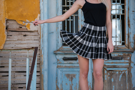 Sexy long slim legs of a woman wearing check mini skirt standing front of an old house Stock Photo