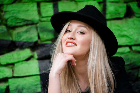 Cute blond teen with long straight hair wear black jacket and hat standing against stone wall with green graffiti Stock Photo