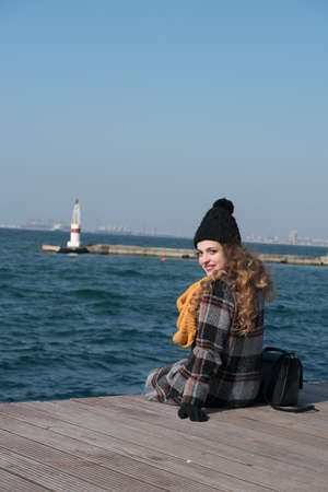 prevailing: Sweet curly teen sitting on the edge of the port wear scarf and skull cap