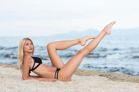 Slim tall gorgeous blonde woman at the beach lying on sand lifting her long legs Stockfoto