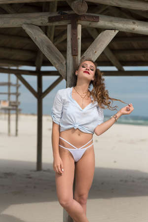 Young cute woman pose against big wooden shelter on the beach wear bottom white bikini and tied shirt
