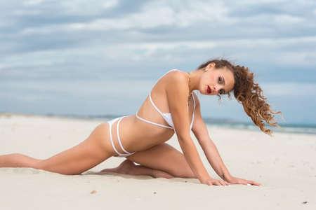 Young cute woman wearing white bikini posing on the beach