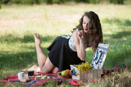 Joyful time of a young beautiful woman having a picnic, wearing a skirt and a sexy deep neckline blouse, preparing her meal Stock Photo