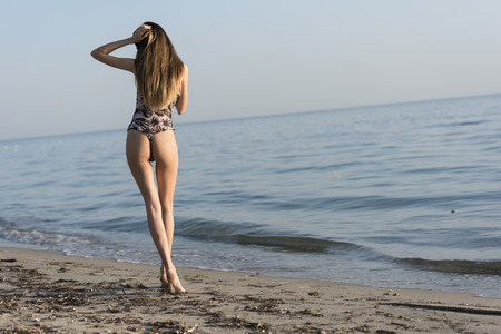 Slim woman wearing monokini, walking in rear view at the sand, full length body in horizontal