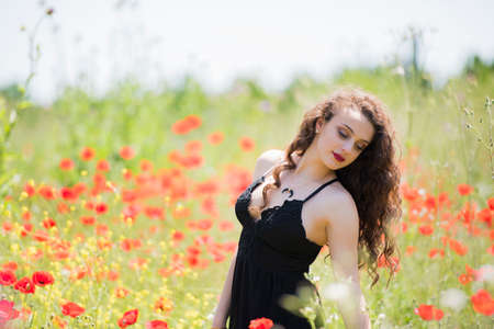 Pretty young lady wear black long dress with deep neckline stands amongst poppies on a farm Stock Photo