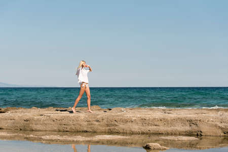 Tall slim blonde woman wear white bottom bikini and long shirt walking on rocks, sea sky and clouds as background
