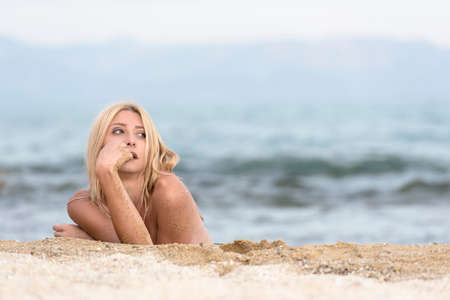 Slim gorgeous blonde woman lying topless on sand, photo in horizontal