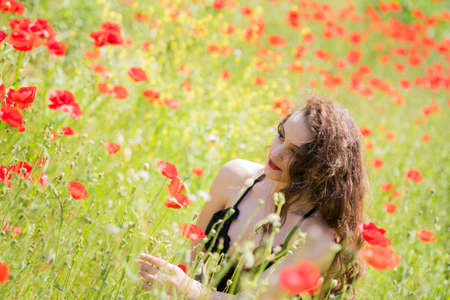 Pretty young lady wear black long dress with deep neckline sitting amongst poppies in a field Stock Photo