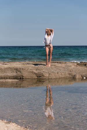 Tall slim blonde woman wear white bottom bikini and long shirt standing on rocks, sea sky and clouds as background