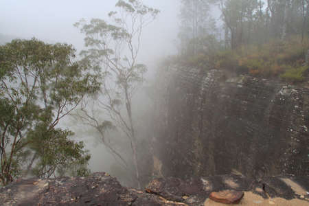 Cliff plumeting into clouds photo