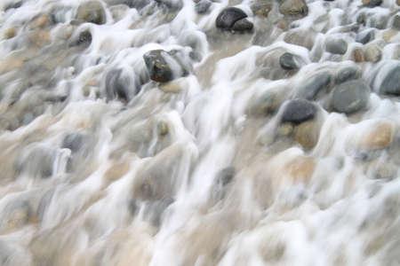 receding: wave receding over rocks