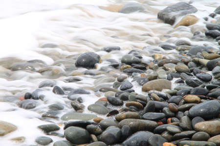 pebble beach: Water retracting from stones