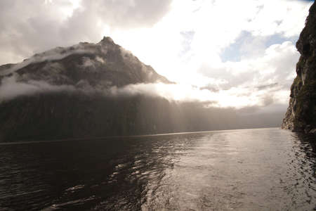 Fog consuming mountain in Milfordsound photo