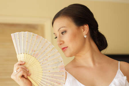 Asian woman fanning herself
