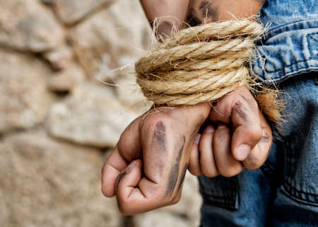 restraints: Dirty hands bound behind back prisoner Stock Photo