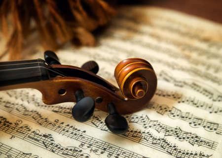Oude houten snaarinstrument viool rust op klassieke bladmuziek. Focus ligt op de rol, stemschroeven, en een deel van de nek.