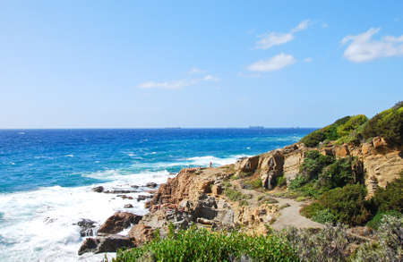 vino: Rocky Italian coastline on a bright blue sky day, with blue water and some coastal vegetation. Strada del Vino Costa degli Etruschi.