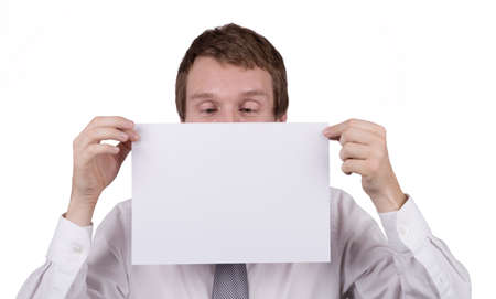 page down: A caucasian male office worker holding a blank piece of paper in front of himself, looking down at the page where a message can be inserted. Isolated on white.