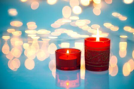 Christmas candles over heavenly background with lights