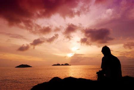 redang: Man sitting on a small island watching the beautiful sunrise  Stock Photo