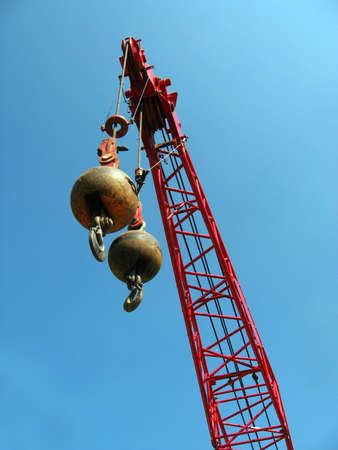 hook up: Two wrecking balls suspended from a red crane, high above the ground, against a blue sky background.