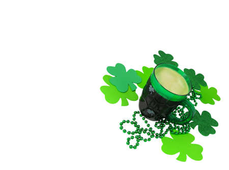 A green plastic party mug for St. Patrick's Day stands with foaming beer among a pile of green beads and shamrock decor. Stock Photo - 9139661