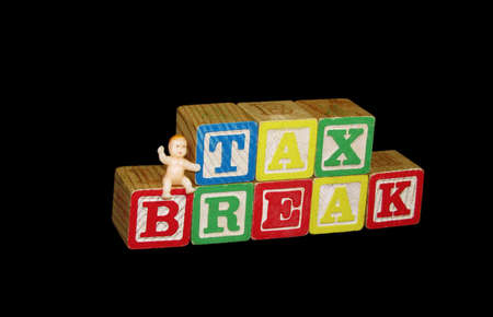 A plastic baby sitting on childrens toy blocks spelling out the phrase tax break.