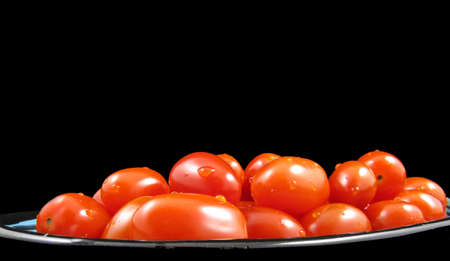 A dish of freshly washed cherry tomatoes isolated on black. Stock Photo - 9257018