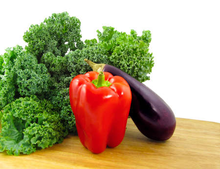 A red bell pepper, a purple eggplant, and a bunch of green kale on a wooden cutting board isolated on white. Stock Photo - 9290724