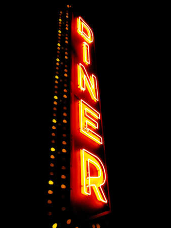 A large neon sign says diner against a black night sky. photo