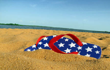 A pair of red, white, and blue flip flops with stars, on a sandy beach with water and sky in the background. photo