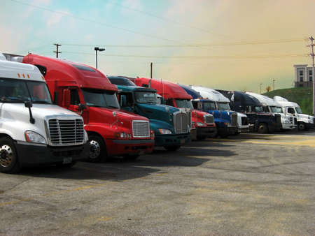 A row of big semi trucks in various colors parked at a truck stop at sunset. Stock Photo