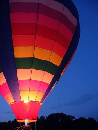 A beautiful multi-colored hot air balloon glows by the light of it's gas fire against a deep blue night sky. Stock Photo - 9655827