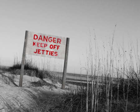 A sign stating Danger Keep Off Jetties with red lettering, in a black and white beach scene wtih sand dunes. Stock Photo - 9988277