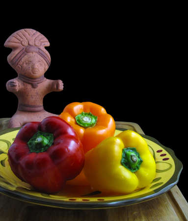 Still life isolated on black of red, yellow, and orange bell peppers on a colorful ceramic dish with a small mayan figure sculpture in the background.                                Stock Photo - 9988279